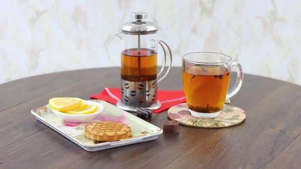 tea kettle with black tea cup with cookies on wooden table background