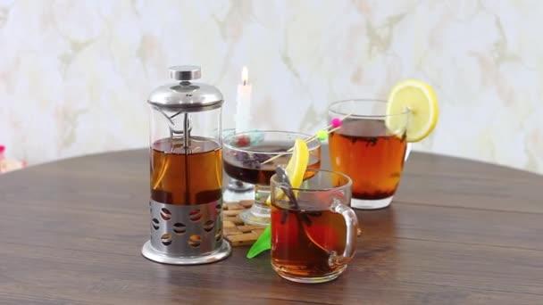 černý čaj konvice s čajovými šálky na dřevěném pozadí