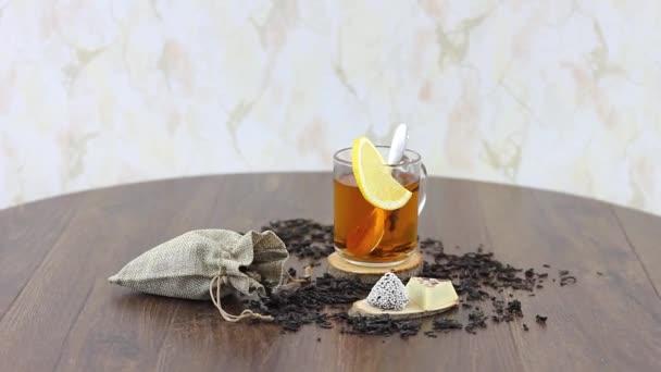 šálek čaje s cukrovinkami a sušené čajové lístky na dřevěném stole pozadí