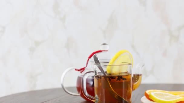 šálek čaje s rychlovarnou konvicí a citrusy na dřevěném stole pozadí