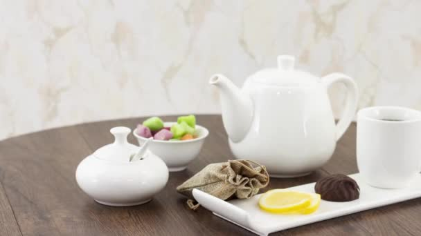 tea kettle with tea cup with candies on wooden table background