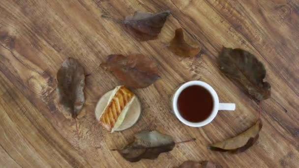 tea cup with bun and dried leaves on wooden table background
