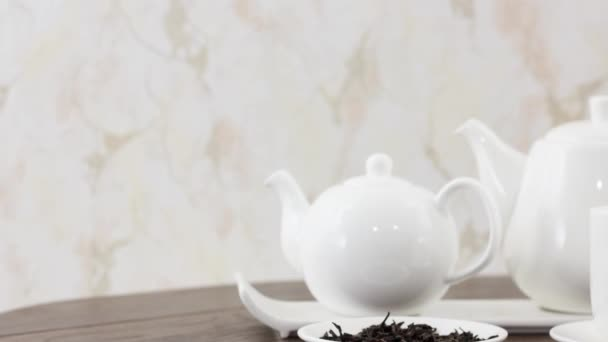 tea cup with kettles and dried leaves on wooden table background