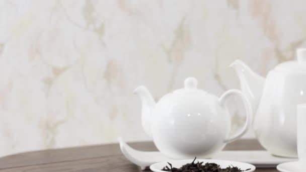 šálek čaje s varnou konvicí a sušenými listy na dřevěném stole pozadí