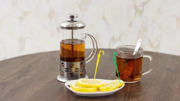 šálek čaje s čajovou konvicí a plátky citronu na dřevěném stole na pozadí