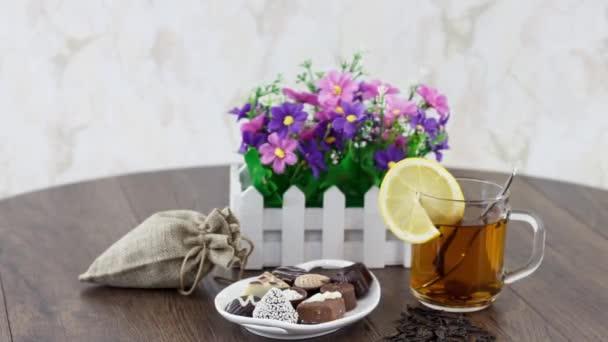 čaj šálek černého silného čaje s bonbóny na pozadí stolu