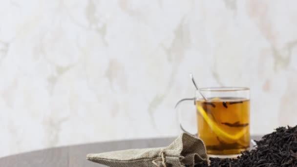 čaj šálek se sušeným čajovým lístkem na dřevěném stole pozadí