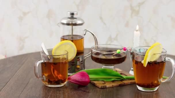 čajové šálky s konvice na čaj a svíčka na dřevěném stole pozadí