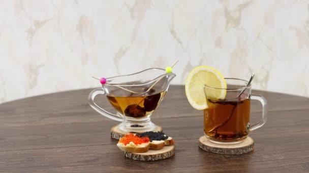 černý šálek čaje s černým a červeným kaviárem na pozadí stolu