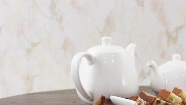 teáskanna és teáscsésze süteményekkel az asztalon háttér