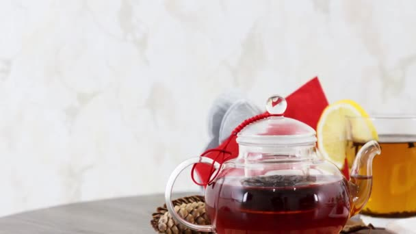 cup of black tea with tea kettle and sweet biscuits on table background