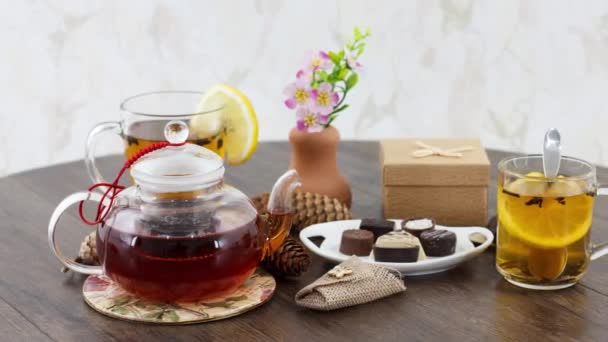 skleněná konvice s šálkem čaje a sladkosti na pozadí stolu