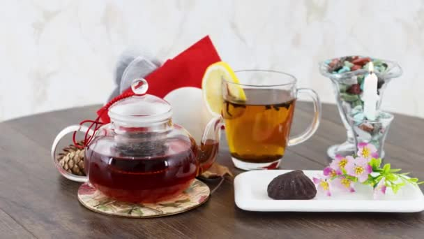 glass kettle with tea cup and sweets on table background