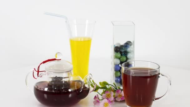 juice glass with tea cup with lemon slice and tea kettle with black tea leaves