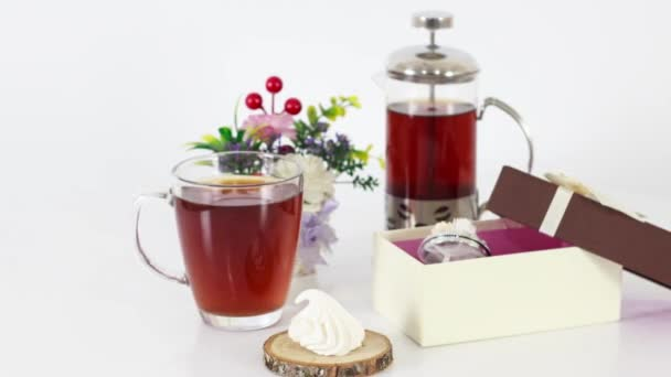 fragrant ceylon black tea cup with teapot and tea sweets on table background