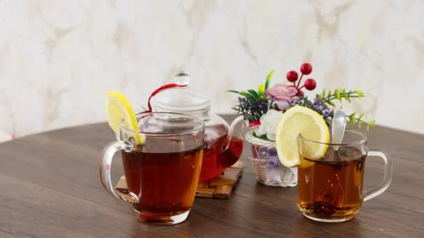 tea cups with lemon slices and kettle on wooden table background