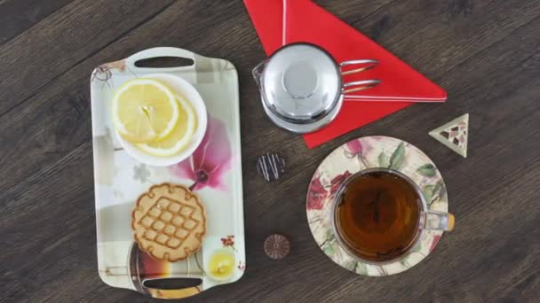 black tea in cup with tea kettle and sweet cookies on table background