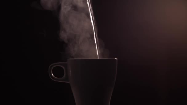 Hot boiled water is poured into a white ceramic cup or mug on black background with light