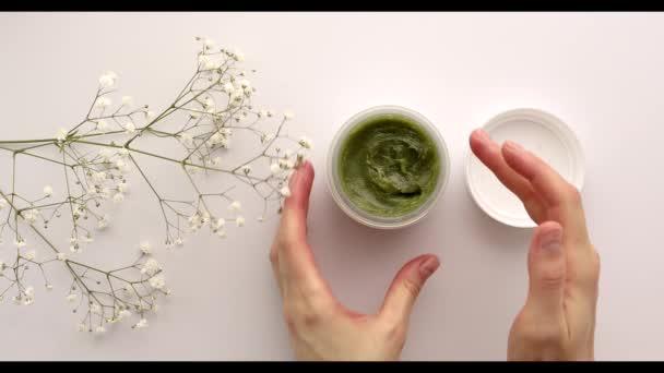 Přírodní kosmetika, kosmetické výrobky, péče o pleť, lázně, ženské ruce používají zelenou masku nebo krém, krém, zblízka. Beauty blogger, salon léčba koncepce.