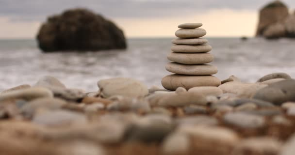 video of Pyramid stones on the seashore on a sunny day on the blue sea background. Happy holidays. Pebble beach, calm sea, travel destination. Concept of happy vacation on the sea.