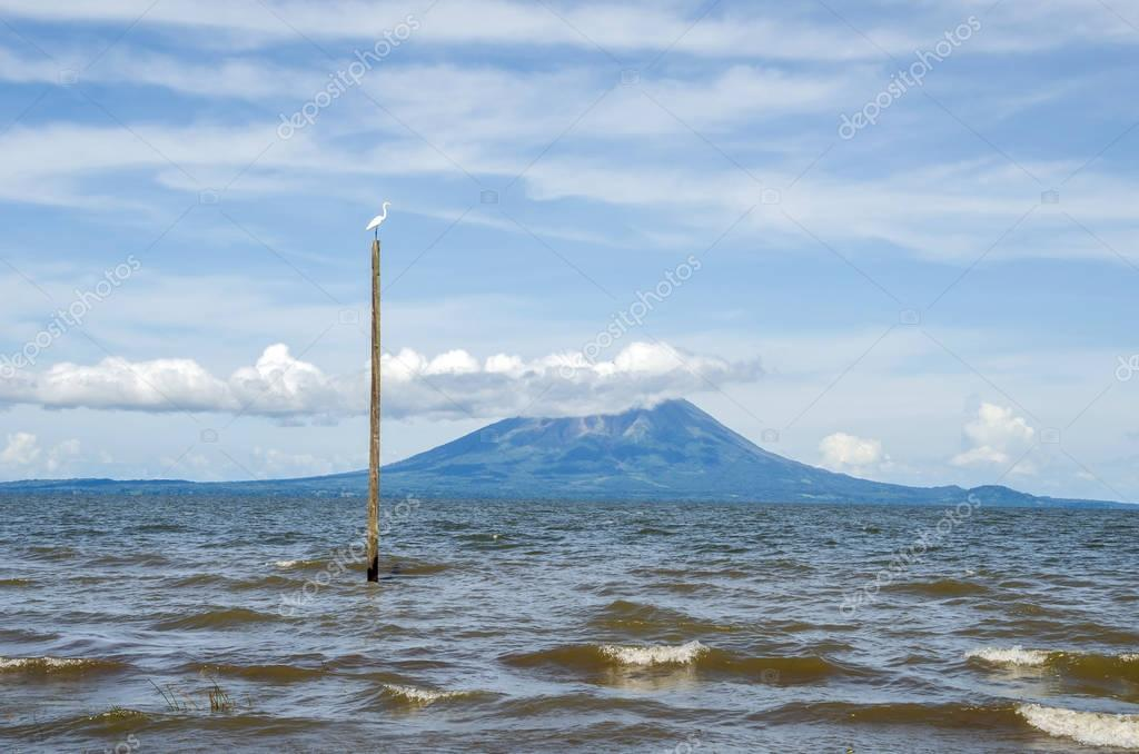 Lake Nicaragua with one of its volcanic islands and a great egret on the top of a post
