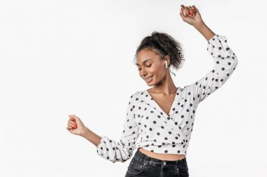 African woman dancing and listening music by earphones in studio over white background