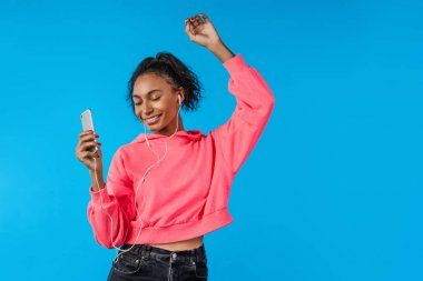 Happy beautiful young african american woman with mobile phone listening to music and dancing over blue background