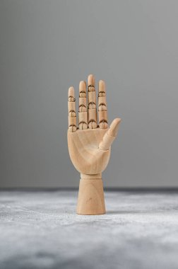 The wooden hand shows five raised fingers. The concept of communication
