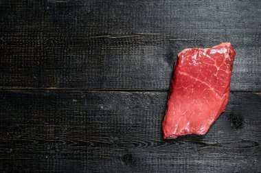 Raw strip loin steak. Beef meat. Black background. Top view. Space for text.