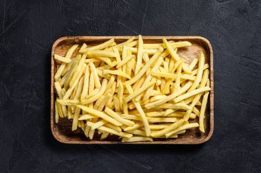 Frozen French fries in a wooden bowl. organic potatoes. Black background. Top view