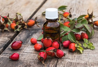 Bottle of rosehip seed essential oil and fresh red berries on a wooden table. Tincture or essential oil with rose hips.