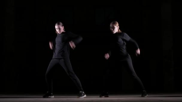 Duett junger schöner Frauen, die Hip-Hop tanzen, Straßentanz auf schwarzem Hintergrund im Studio, isoliert