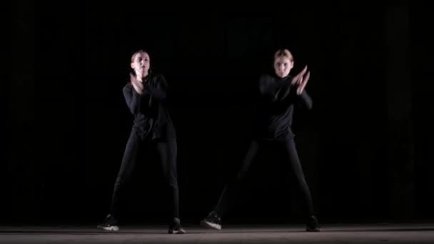 duett fiatal gyönyörű nők táncoló hip hop, utcai tánc egy fekete háttér a stúdióban, elszigetelt
