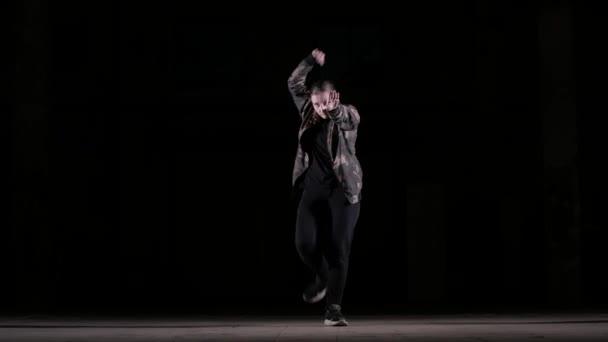 Fiatal gyönyörű lány táncol hip hop, utcai tánc a stúdióban a fekete háttér, elszigetelt
