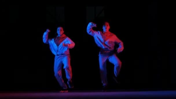 duett fiatal gyönyörű lányok táncoló hip hop, utcai tánc a stúdióban egy fekete háttér, elszigetelt