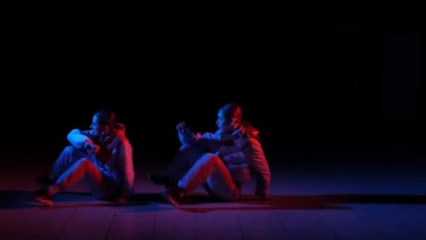 duet mladých krásných dívek tančících hip hop, street dance v ateliéru na černém pozadí, izolované