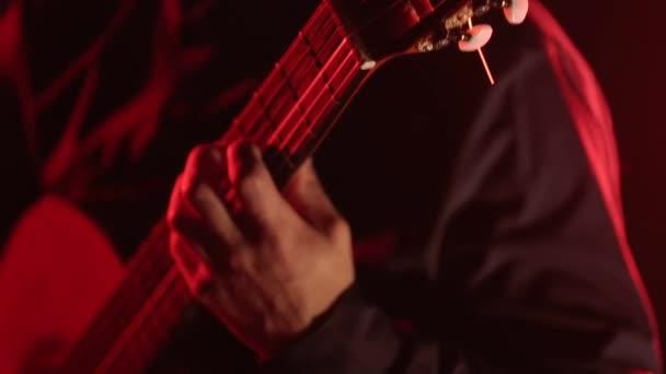 ruce kytaristy hrajícího na klasickou kytaru, detailní záběr na struny kytary a krk