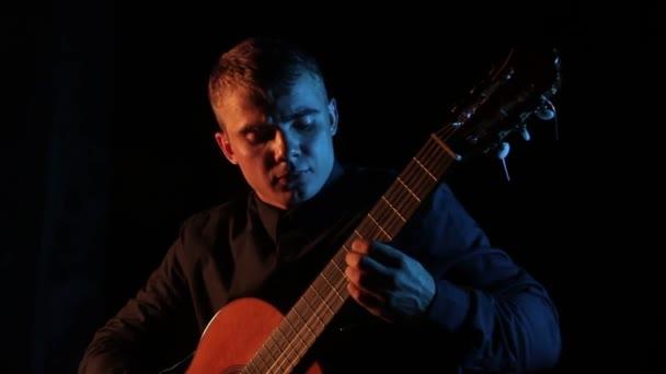 zenész virtuóz játszik a klasszikus akusztikus gitár egy fekete háttér, közelkép az arc, elszigetelt