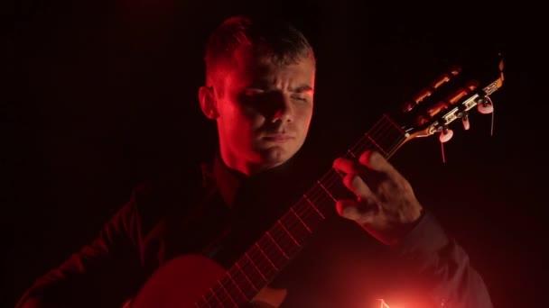 Gitarrist spielt leidenschaftlich Akustikgitarre auf schwarzem Hintergrund, Nahaufnahme des Gesichts, isoliert