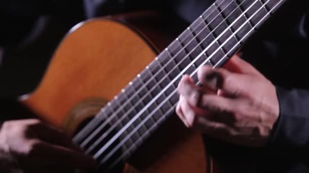 Nahaufnahme von Saiten und Griffbrett, Gitarrist spielt Akustikgitarre