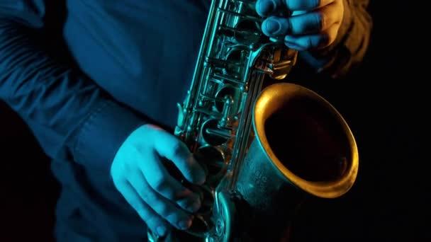 Közel egy virtuóz szaxofonos kezéhez, aki gyorsan játszik hangszeren. A profi zenész megujjazza a billentyűket. Fekete háttér