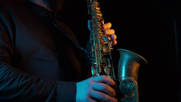 Az ember ujjai játszanak a szaxofon gyönyörű blues dallamot. Közelről. Fekete háttér