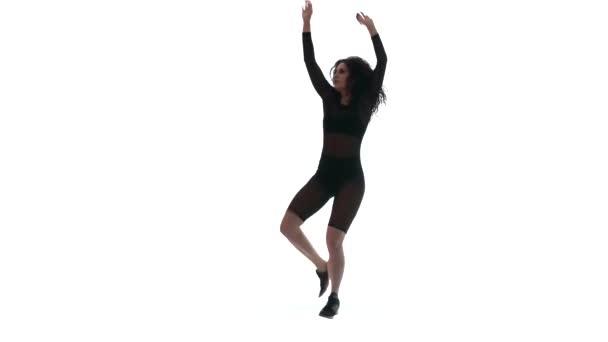 Silhouette eines jungen schönen Mädchens in einem schwarzen transparenten engen Anzug, das energisch Dancehall, Streetdance, Twerk vor weißem Hintergrund tanzt, isoliert, Zeitlupe