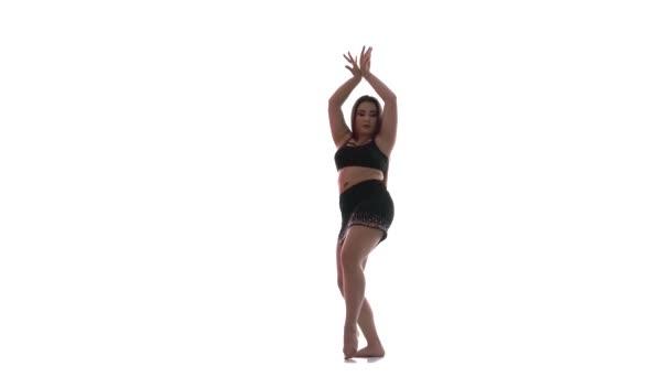 junges schönes Mädchen mit langen Haaren und einer schönen dicken Figur in schwarzem Top und kurzem schwarzen Rock tanzt Bauchtanz, orientalischer Tanz, exotischer Tanz auf weißem Hintergrund, isoliert