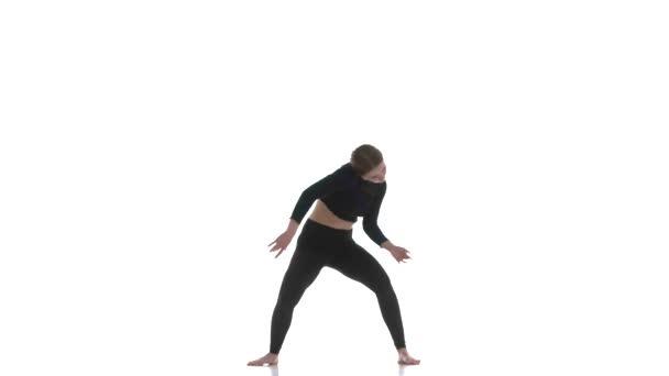 junge schöne Tänzerin in schwarzem kurzen Top und schwarzen Leggings tanzt zeitgenössischen, modernen Balletttanz, isoliert, Zeitlupe