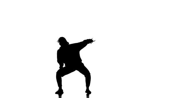 fekete sziluett fehér háttérrel, fiatal gyönyörű lány táncos melegítőben és baseball sapka tánc hip hop, kortárs, modern utcai tánc, lassított felvétel