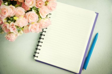 Empty notebook with pen and flower. Abstract background.
