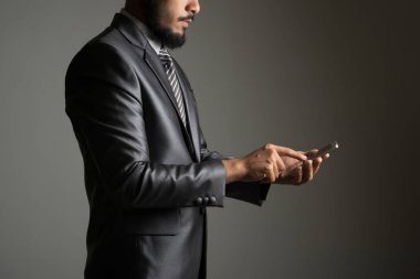 Young businessman using mobile phone isolated on black.
