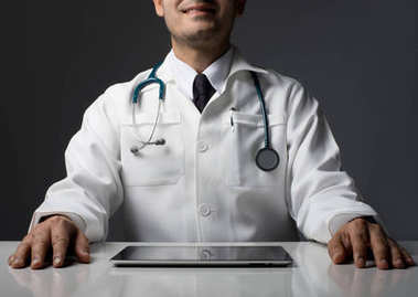 Male medical Doctor hands with tablet computer sitting isolated on black.
