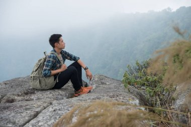 Young hipster Hiker with backpack sitting on top of the mountain